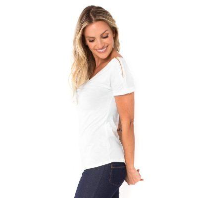 A modelo mostra a parte lateral blusa para amamentar branca. A blusa possui ziper nos ombros para facilitar a amamentação.