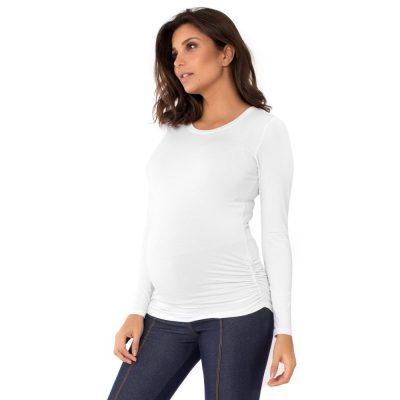 Parte lateral da blusa para grávidas branca com a manga longa e drapeado lateral, vestida por uma modelo que está de lado.