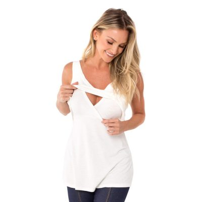 A modelo mostra o detalhe da blusa para amamentar branca. A blusa possui sobreposição para facilitar a amamentação.