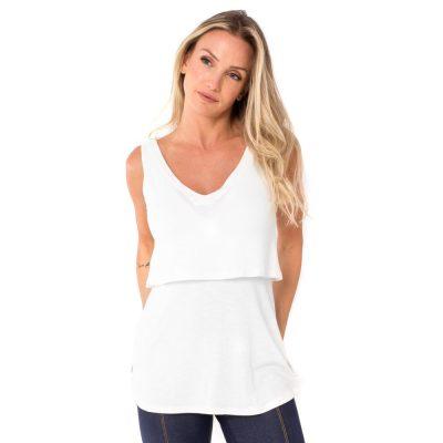 A modelo mostra a frente da blusa para amamentar branca. A blusa possui sobreposição para facilitar a amamentação.