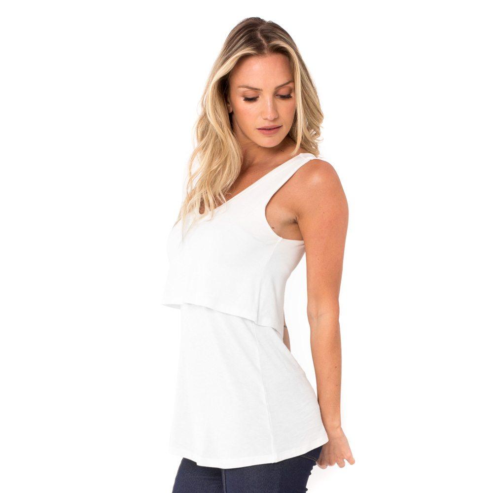 A modelo mostra a parte lateral blusa para amamentar branca. A blusa possui sobreposição para facilitar a amamentação.