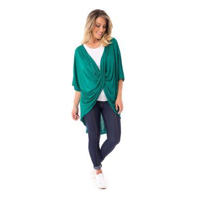 A modelo mostra a parte lateral da blusa para amamentar verde. A blusa possui a parte de trás mais alongada.